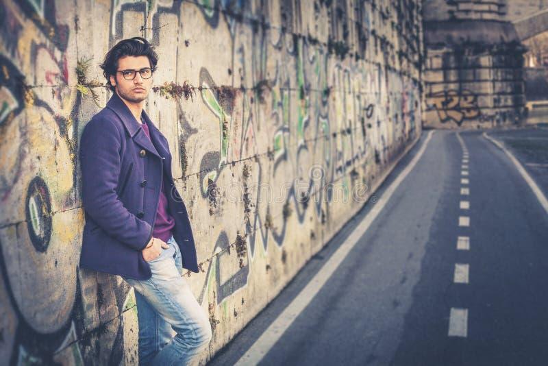 Ο όμορφος και γοητευτικός νεαρός άνδρας κλίνει υπαίθρια ενάντια σε έναν τοίχο στην πόλη στοκ φωτογραφία με δικαίωμα ελεύθερης χρήσης