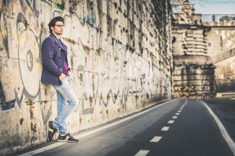 Ο όμορφος και γοητευτικός νεαρός άνδρας κλίνει υπαίθρια ενάντια σε έναν τοίχο στην πόλη στοκ φωτογραφία