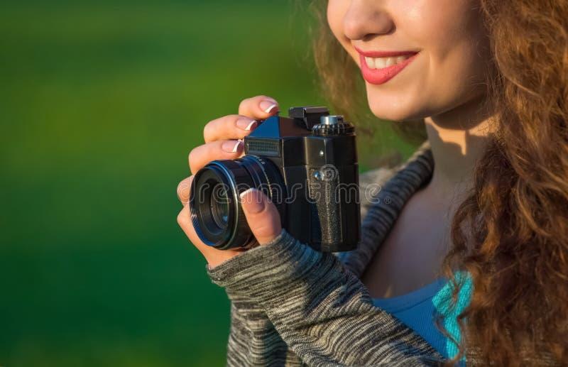 Ο όμορφος κορίτσι-φωτογράφος με τη σγουρή τρίχα που κρατά μια παλαιά κάμερα και παίρνει μια εικόνα, την άνοιξη υπαίθρια στο πάρκο στοκ εικόνες