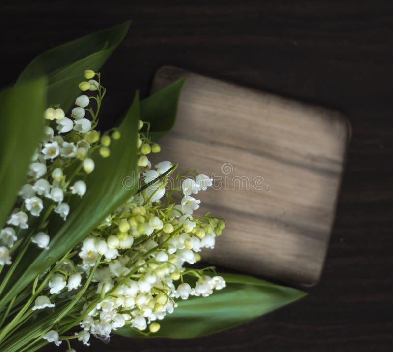 Ο όμορφος κρίνος των λουλουδιών κοιλάδων σε ένα σκοτεινό κατασκευασμένο υπόβαθρο με ένα σημάδι για το επίπεδο επιγραφής βάζει, το στοκ εικόνες
