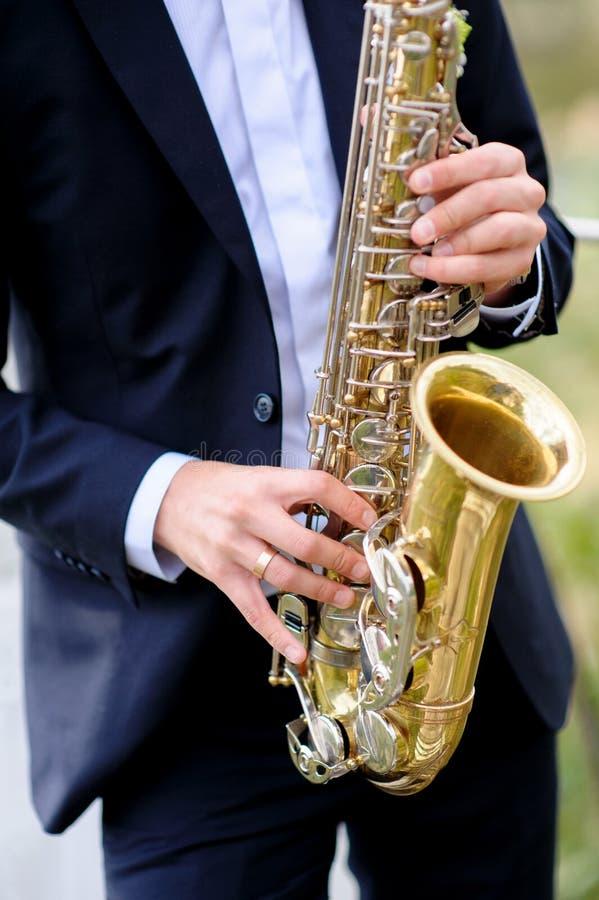 Ο όμορφος μουσικός παίζει το saxophone στοκ φωτογραφίες