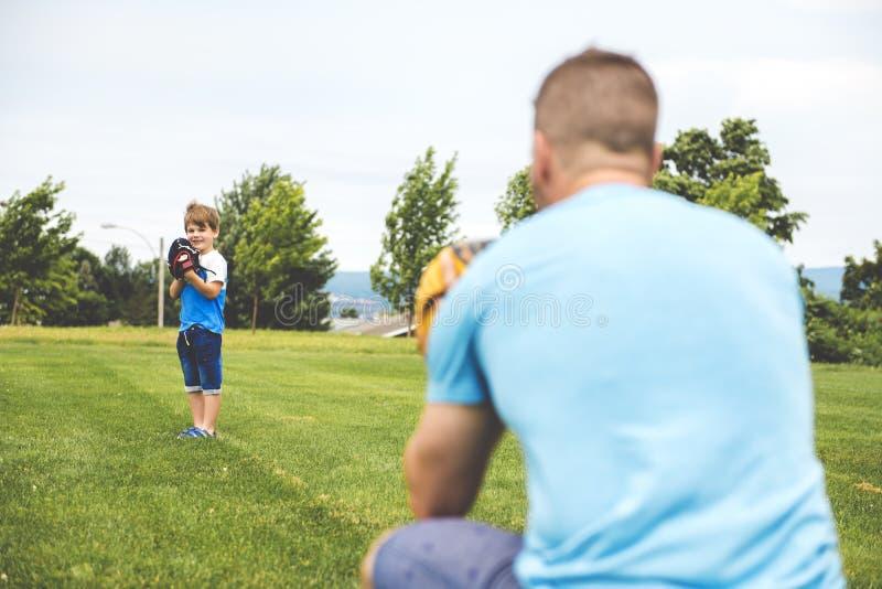 Ο όμορφος μπαμπάς με το μικρό χαριτωμένο ήλιό του παίζει το μπέιζ-μπώλ στον πράσινο χλοώδη χορτοτάπητα στοκ εικόνες