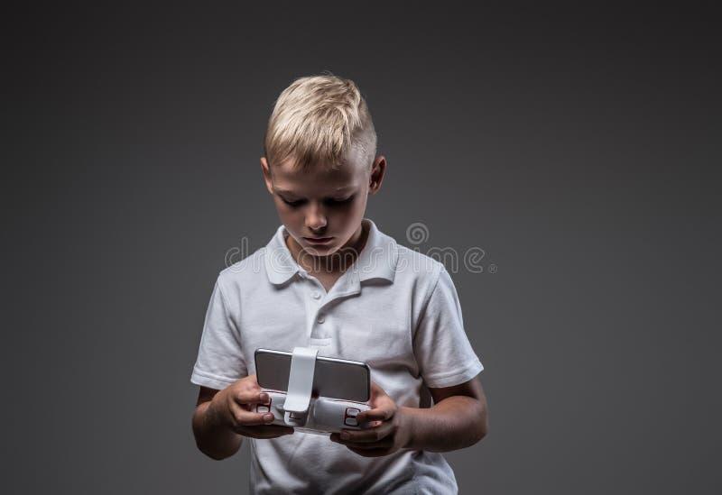 Ο όμορφος μπόξερ μικρών παιδιών με την ξανθή τρίχα που ντύνεται σε μια άσπρη μπλούζα κρατά έναν έλεγχο quadcopter μακρινό στοκ εικόνες