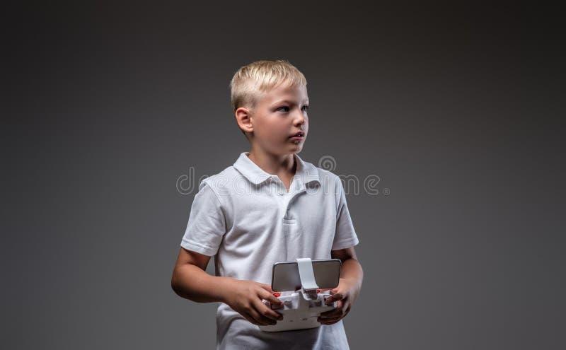 Ο όμορφος μπόξερ μικρών παιδιών με την ξανθή τρίχα που ντύνεται σε μια άσπρη μπλούζα κρατά έναν έλεγχο quadcopter μακρινό στοκ εικόνα με δικαίωμα ελεύθερης χρήσης