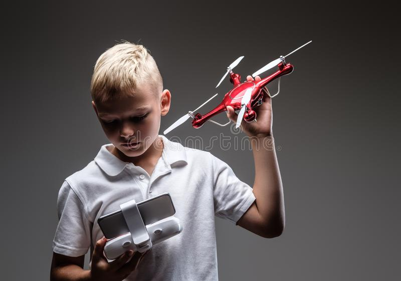 Ο όμορφος μπόξερ μικρών παιδιών με την ξανθή τρίχα που ντύνεται σε μια άσπρη μπλούζα κρατά ένα quadcopter και έναν έλεγχο μακρινο στοκ εικόνα