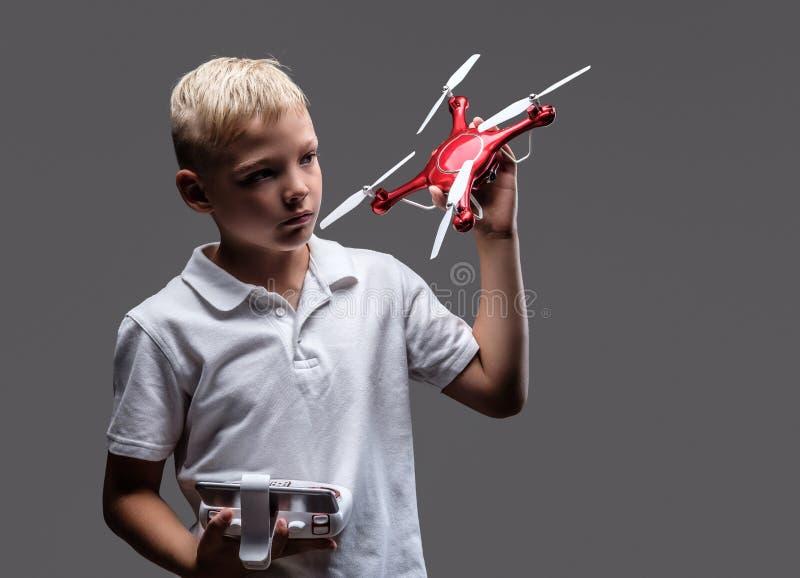 Ο όμορφος μπόξερ μικρών παιδιών με την ξανθή τρίχα που ντύνεται σε μια άσπρη μπλούζα κρατά ένα quadcopter και έναν έλεγχο μακρινο στοκ φωτογραφίες με δικαίωμα ελεύθερης χρήσης