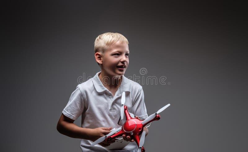 Ο όμορφος μπόξερ μικρών παιδιών με την ξανθή τρίχα που ντύνεται σε μια άσπρη μπλούζα κρατά ένα quadcopter και έναν έλεγχο μακρινο στοκ φωτογραφίες