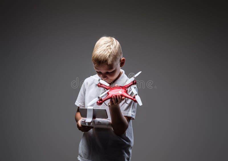Ο όμορφος μπόξερ μικρών παιδιών με την ξανθή τρίχα που ντύνεται σε μια άσπρη μπλούζα κρατά ένα quadcopter και έναν έλεγχο μακρινο στοκ εικόνες