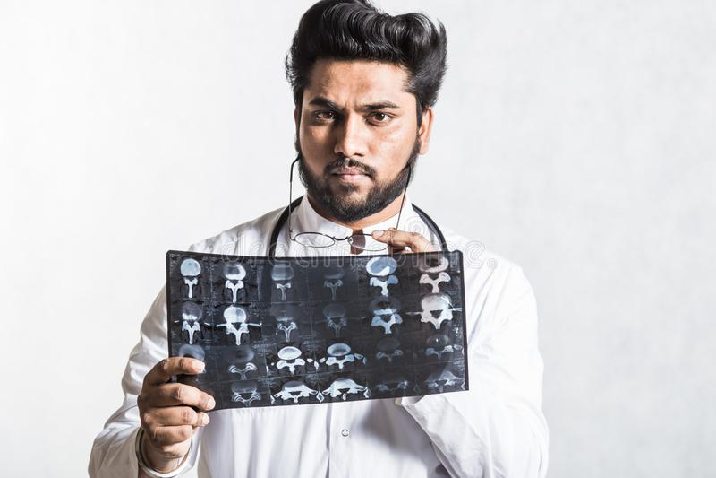 Ο όμορφος νέος γιατρός σε ένα άσπρο παλτό με ένα στηθοσκόπιο ελέγχει προσεκτικά την ακτίνα X του ασθενή στοκ φωτογραφίες