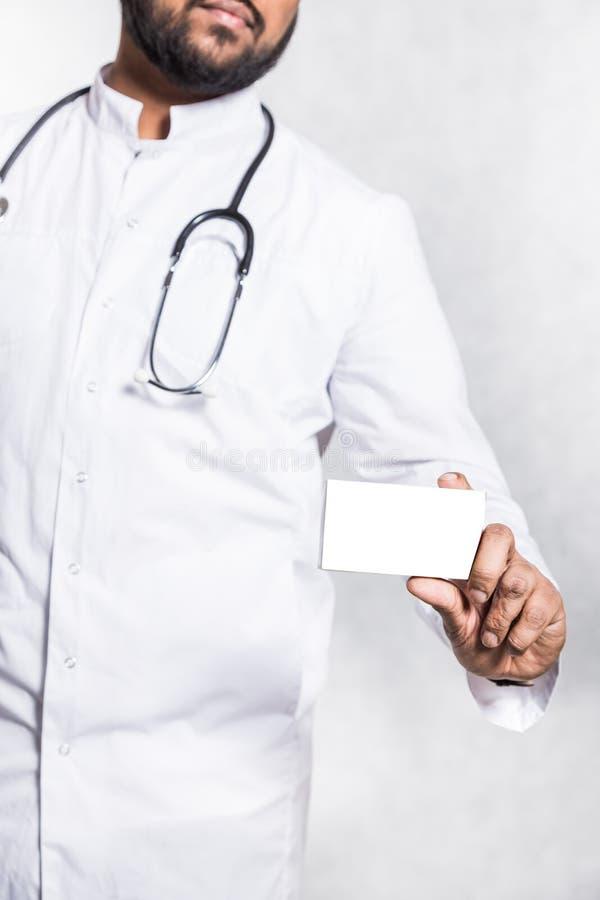Ο όμορφος νέος γιατρός σε ένα άσπρο παλτό με ένα στηθοσκόπιο κρατά το χέρι ένα κενό άσπρο κιβώτιο συσκευασίας για στοκ φωτογραφία με δικαίωμα ελεύθερης χρήσης