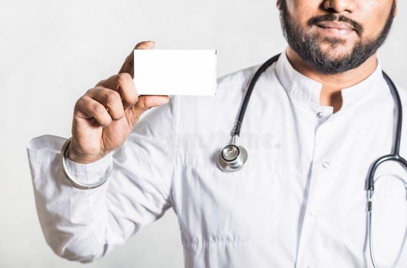 Ο όμορφος νέος γιατρός σε ένα άσπρο παλτό με ένα στηθοσκόπιο κρατά το χέρι ένα κενό άσπρο κιβώτιο συσκευασίας για στοκ εικόνες με δικαίωμα ελεύθερης χρήσης