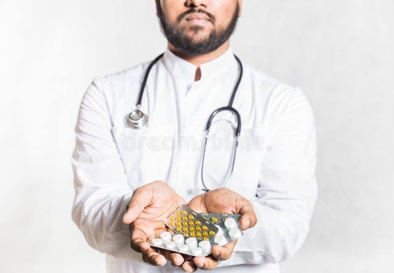 Ο όμορφος νέος γιατρός σε ένα άσπρο παλτό με ένα στηθοσκόπιο κρατά το χ στοκ εικόνα