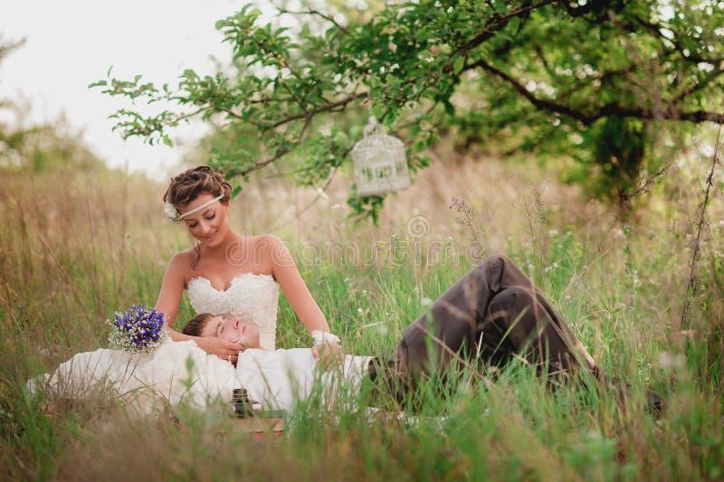Ο όμορφος νέος νεόνυμφος φιλά και αγκαλιάζει τη νύφη στοκ εικόνα