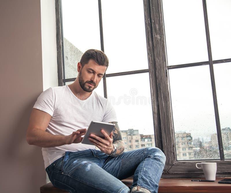 Ο όμορφος νέος τύπος κάθεται από το παράθυρο και κάνει τις σημειώσεις στη σκέψη ταμπλετών του στοκ φωτογραφία με δικαίωμα ελεύθερης χρήσης