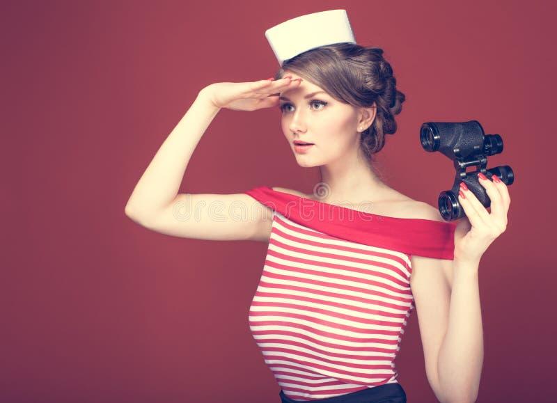 Ο όμορφος ναυτικός κοριτσιών με εκλεκτής ποιότητας διόπτρες και εξετάζει την απόσταση στοκ φωτογραφία