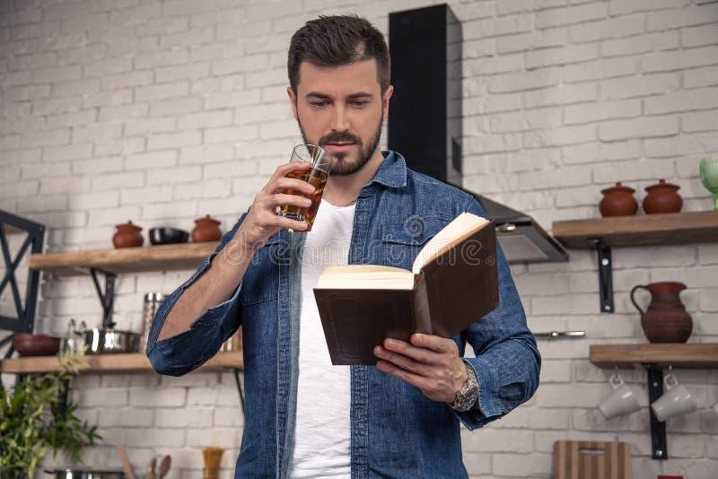 Ο όμορφος νεαρός άνδρας πίνει έναν χυμό μήλων και διαβάζει ένα βιβλίο στην κουζίνα στοκ εικόνες