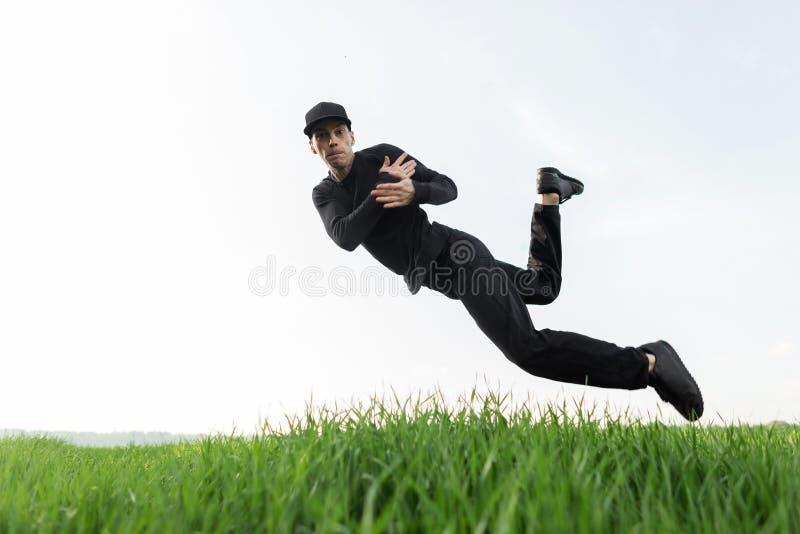 Ο όμορφος νεαρός άνδρας στα μαύρα ενδύματα στη μοντέρνη ΚΑΠ θέτει στον αέρα υπαίθρια Μοντέρνος τύπος στο άλμα στοκ φωτογραφίες με δικαίωμα ελεύθερης χρήσης