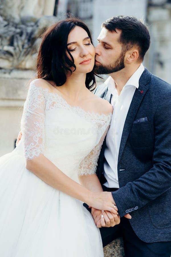 Ο όμορφος νεόνυμφος φιλά μαλακά την πανέμορφη νύφη στο μάγουλο Αισθησιακό υπαίθριο πορτρέτο στοκ φωτογραφία με δικαίωμα ελεύθερης χρήσης
