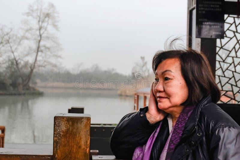 Ο όμορφος παλαιός ασιατικός ταξιδιώτης γυναικών πολύ χαλαρώνει και ήρεμος στο πάρκο της πόλης hangzhou στοκ φωτογραφίες