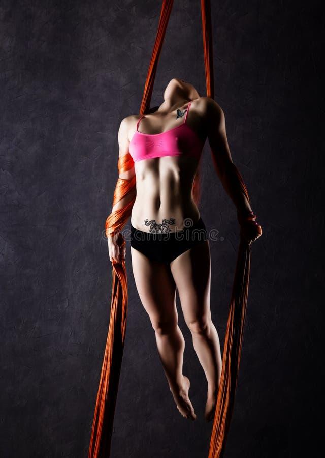 Ο όμορφος προκλητικός χορευτής στο εναέριο μετάξι, χαριτωμένη παραμόρφωση, ακροβάτης εκτελεί ένα τέχνασμα κορδέλλες στοκ εικόνα