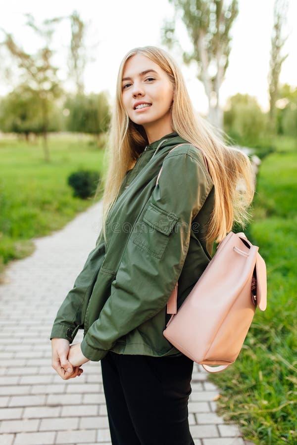 Ο όμορφος σπουδαστής κοριτσιών, έντυσε σε ένα σακάκι με έναν χαρτοφύλακα, wa στοκ εικόνες
