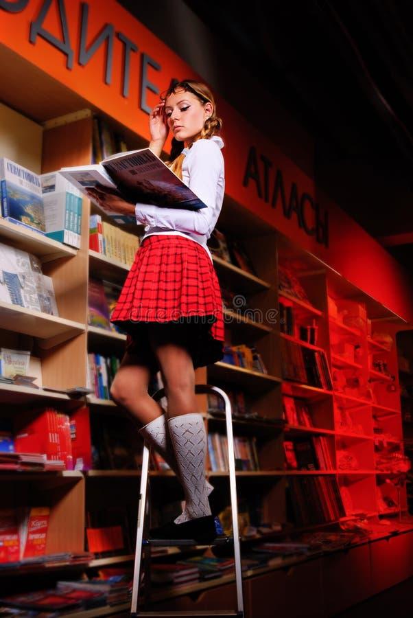 Ο όμορφος σπουδαστής στη βιβλιοθήκη. στοκ εικόνα με δικαίωμα ελεύθερης χρήσης