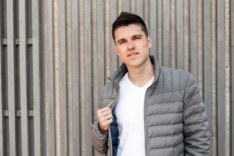 Ο όμορφος σύγχρονος νεαρός άνδρας με ένα μοντέρνο hairstyle σε ένα μοντέρνο γκρίζο σακάκι σε μια καθιερώνουσα τη μόδα άσπρη μπλού στοκ εικόνα