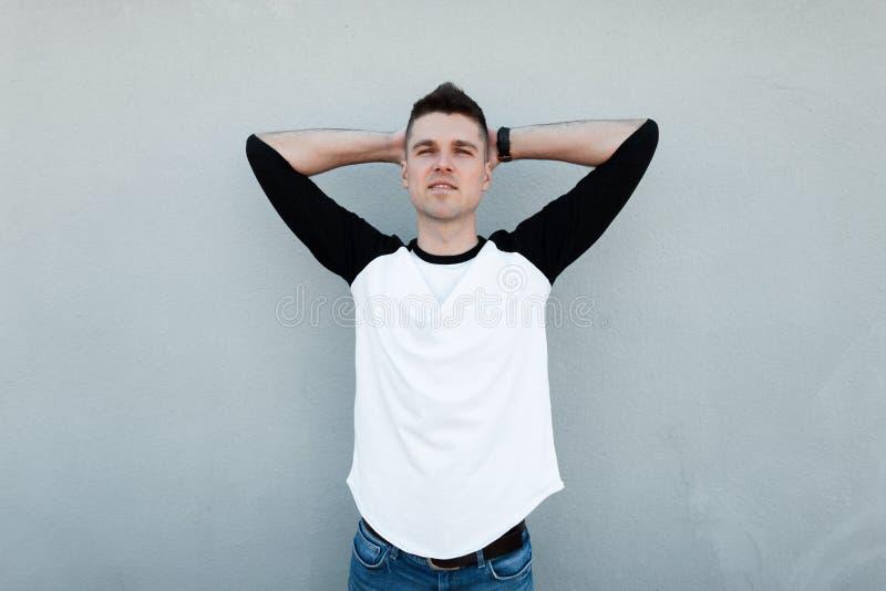 Ο όμορφος σύγχρονος νεαρός άνδρας με ένα μοντέρνο hairstyle σε μια μοντέρνη γραπτή μπλούζα στα εκλεκτής ποιότητας τζιν θέτει στοκ φωτογραφίες