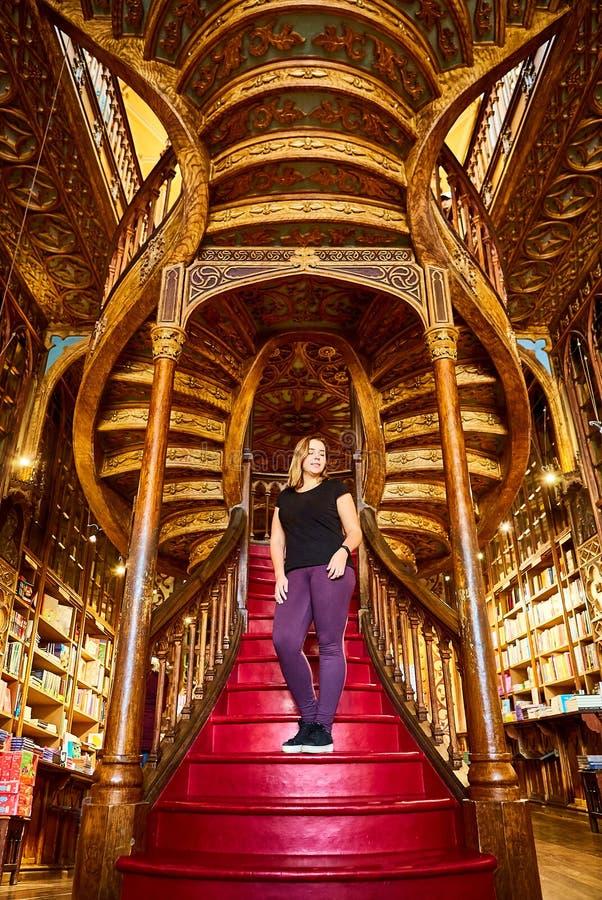 Ο όμορφος τουρίστας γυναικών στέκεται στη μεγάλη ξύλινη σκάλα με τα κόκκινα βήματα μέσα στο βιβλιοπωλείο Livraria Lello βιβλιοθηκ στοκ φωτογραφία