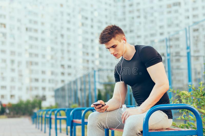 Ο όμορφος τύπος στην αθλητική μαύρη μπλούζα και τα γκρίζα αθλητικά εσώρουχα κάθεται στον πάγκο στο υπόβαθρο πόλεων και σταδίων Εί στοκ φωτογραφία με δικαίωμα ελεύθερης χρήσης
