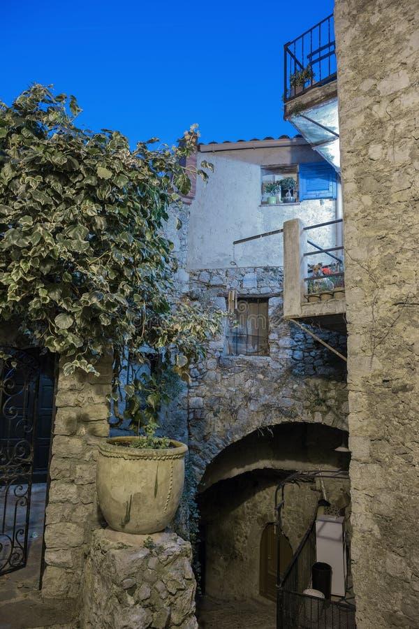 Οδός με τα λουλούδια στην παλαιά πόλη Peille στη Γαλλία στοκ φωτογραφία