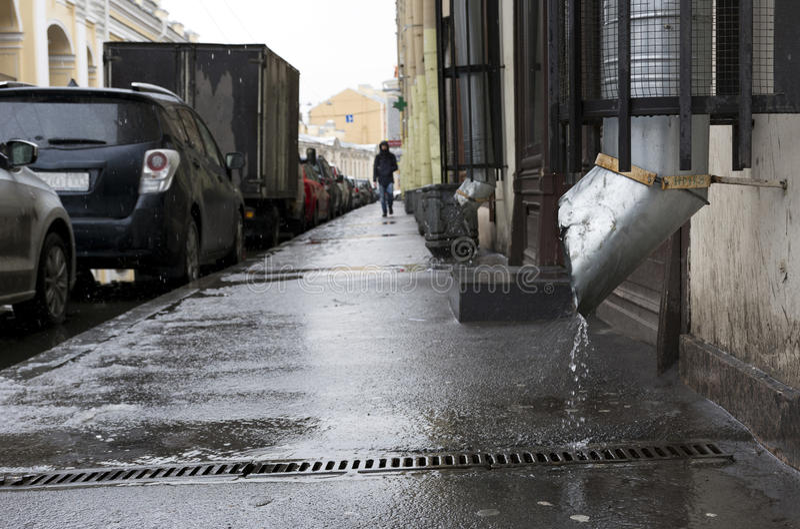 Οδός πόλεων, άτομο που περπατά στο πεζοδρόμιο, η βροχή, αυτοκίνητα που σταθμεύουν στοκ εικόνα