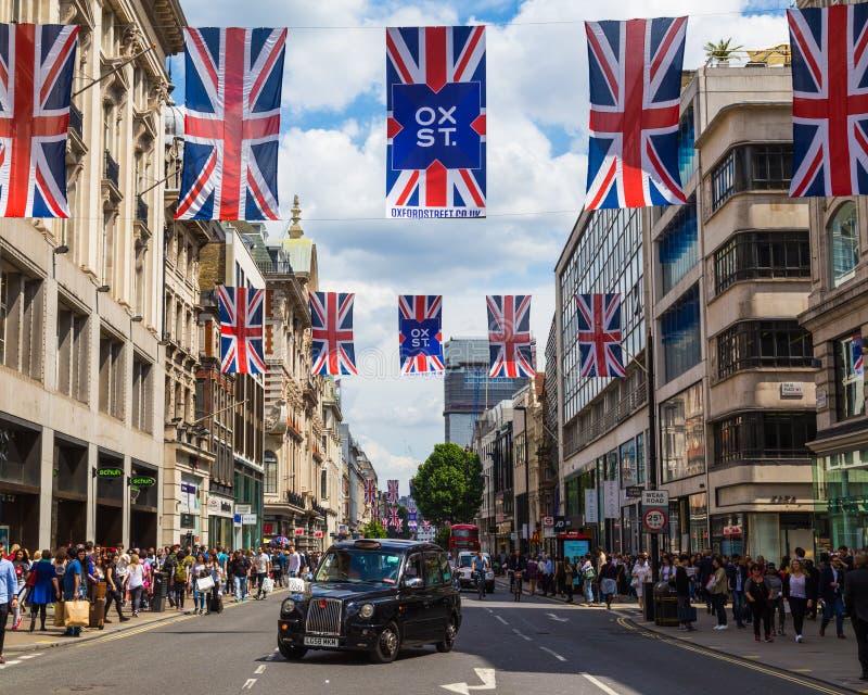 Οδός της Οξφόρδης, σημαίες του Union Jack, Taxi' s και άνθρωποι στοκ εικόνες