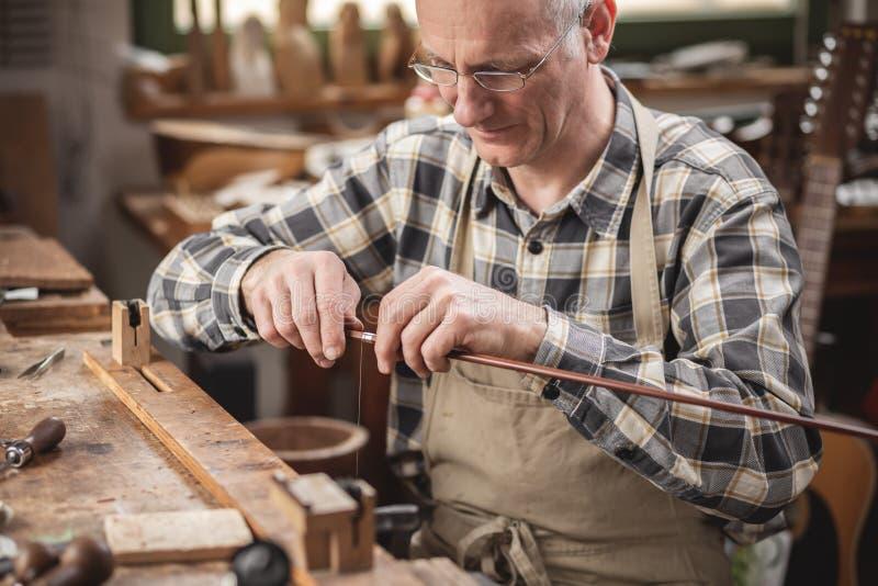 Ο ώριμος κατασκευαστής οργάνων μέσα σε ένα αγροτικό εργαστήριο τυλίγει ένα καλώδιο γύρω από ένα τόξο βιολιών στοκ εικόνες