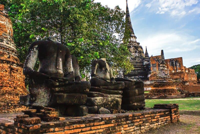 Ο Headless Βούδας στην τοποθέτηση των καταστροφών αγαλμάτων περισυλλογής στο ιστορικό πάρκο Wat Phra Sri Sanphet, επαρχία Ayuttha στοκ φωτογραφία