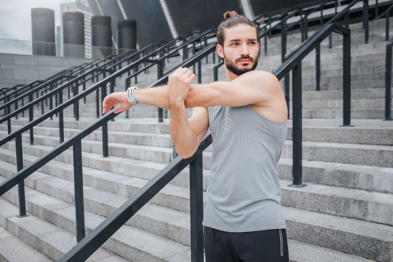 Ο Muscled και ισχυρός νέος αθλητικός τύπος στέκεται και τεντώνει τα χέρια του Ο τύπος κοιτάζει στο δικαίωμα Συγκεντρώνεται σοβαρό στοκ εικόνες