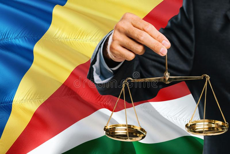 Ο Seychellois δικαστής κρατά τις χρυσές κλίμακες της δικαιοσύνης με τις Σεϋχέλλες που κυματίζουν το υπόβαθρο σημαιών Θέμα ισότητα στοκ φωτογραφίες με δικαίωμα ελεύθερης χρήσης