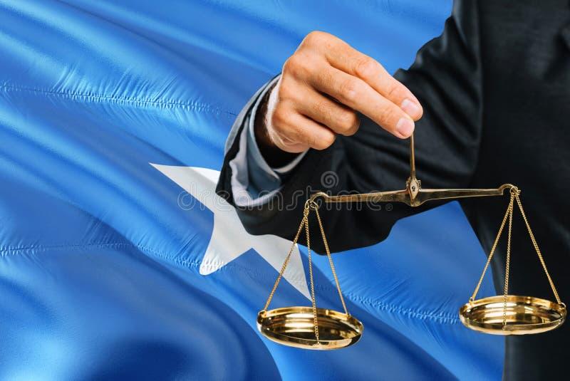 Ο Somalian δικαστής κρατά τις χρυσές κλίμακες της δικαιοσύνης με το κυματίζοντας υπόβαθρο σημαιών της Σομαλίας Θέμα ισότητας και  στοκ εικόνα