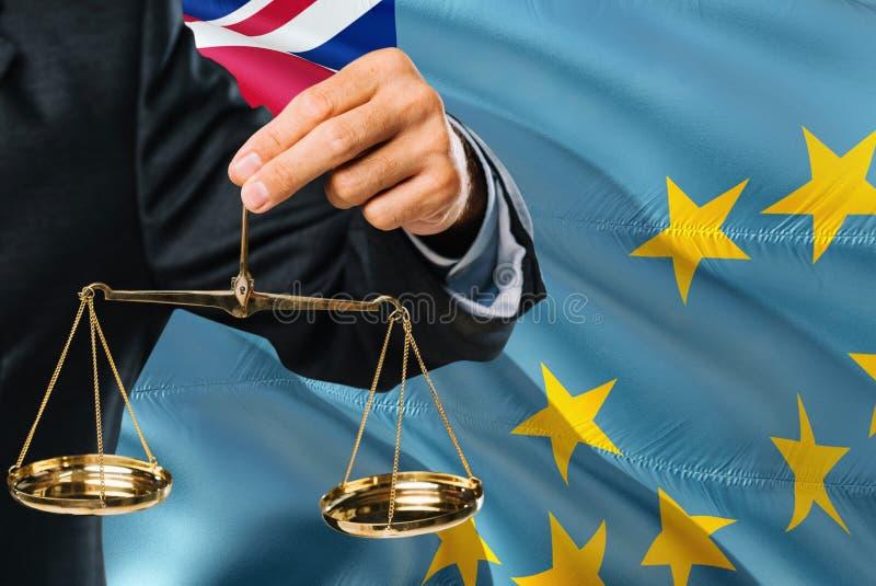 Ο Tuvaluan δικαστής κρατά τις χρυσές κλίμακες της δικαιοσύνης με το κυματίζοντας υπόβαθρο σημαιών του Τουβαλού Θέμα ισότητας και  στοκ εικόνες