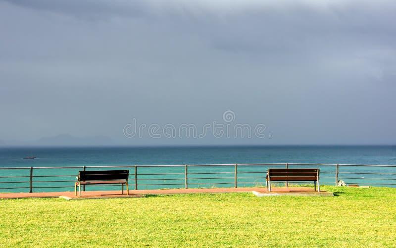 Πάγκοι στον απότομο βράχο με τη θάλασσα και τα θυελλώδη σύννεφα στοκ φωτογραφίες