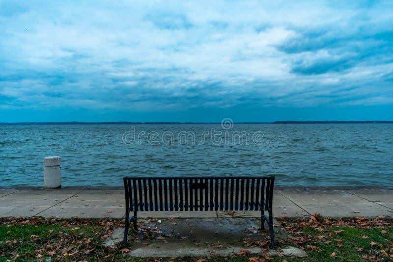 Πάγκος που αντιμετωπίζει προς τη λίμνη Mendota κατά τη διάρκεια ενός κρύου σκοτεινού βραδιού στοκ φωτογραφία με δικαίωμα ελεύθερης χρήσης