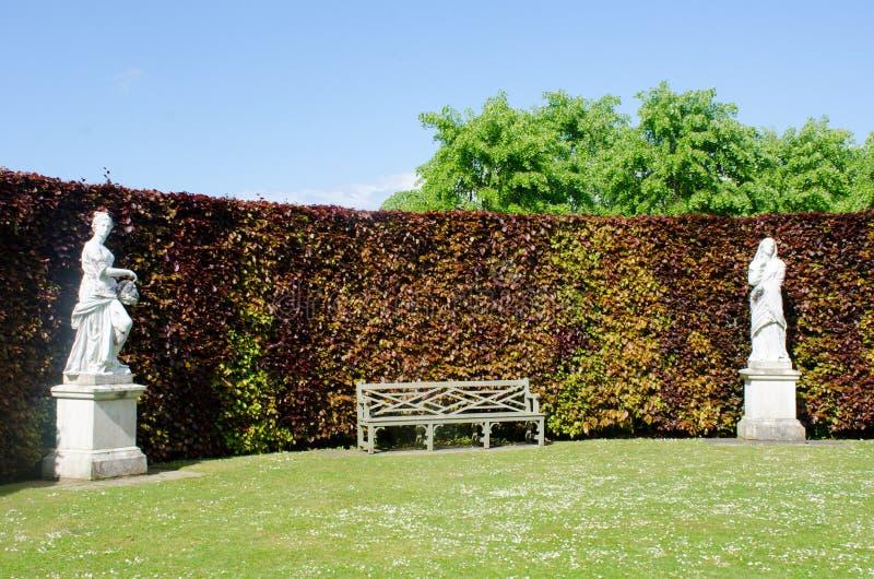Πάγκος που πλαισιώνεται από τα αγάλματα στον αγγλικό κήπο χωρών στοκ εικόνες