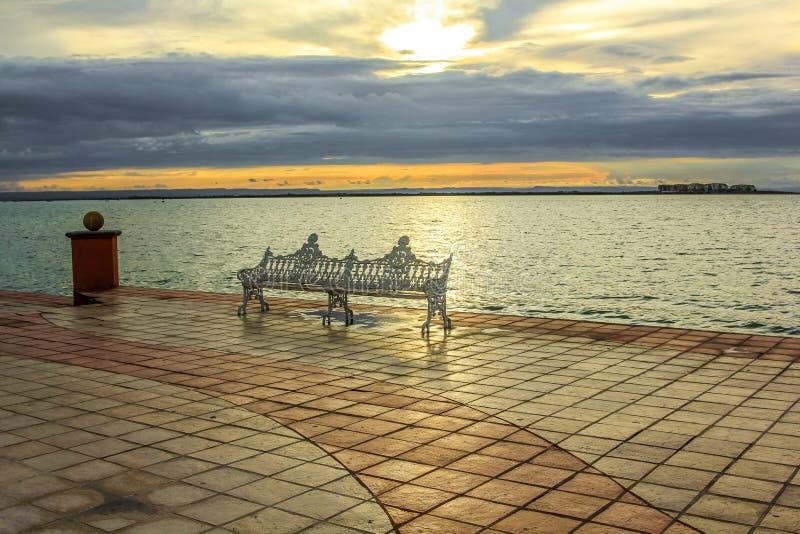 Πάγκος σιδήρου στην προκυμαία στο ηλιοβασίλεμα στοκ φωτογραφίες