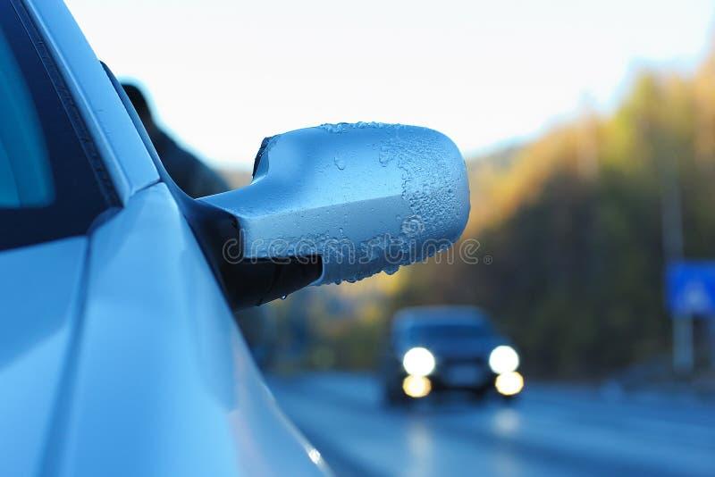 Πάγος-καλυμμένος οπισθοσκόπος καθρέφτης αυτοκινήτων ενάντια στο δρόμο στοκ εικόνες