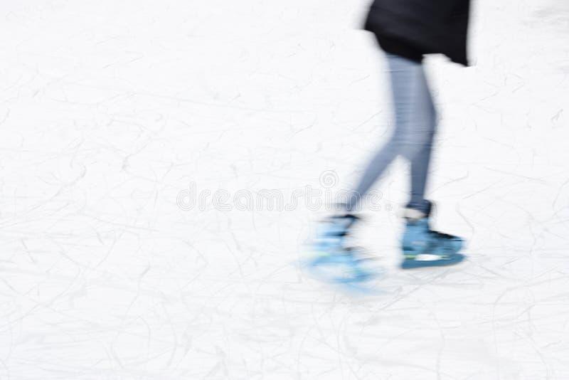 Πάγος νεαρών ατόμων που κάνει πατινάζ, πόδια στη θαμπάδα κινήσεων στοκ εικόνες