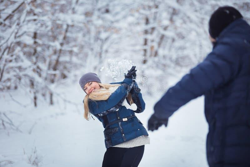 Πάλη χιονιών Χειμερινό ζεύγος που έχει το παιχνίδι διασκέδασης στο χιόνι υπαίθρια στοκ φωτογραφίες