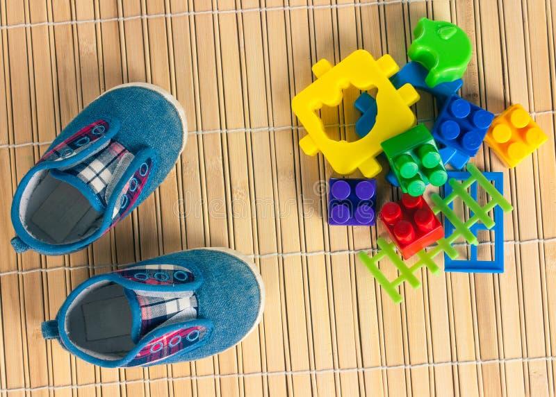 Πάνινα παπούτσια και χρωματισμένα παιχνίδια σε ένα πάτωμα σκληρού ξύλου κορυφαία όψη στοκ εικόνες