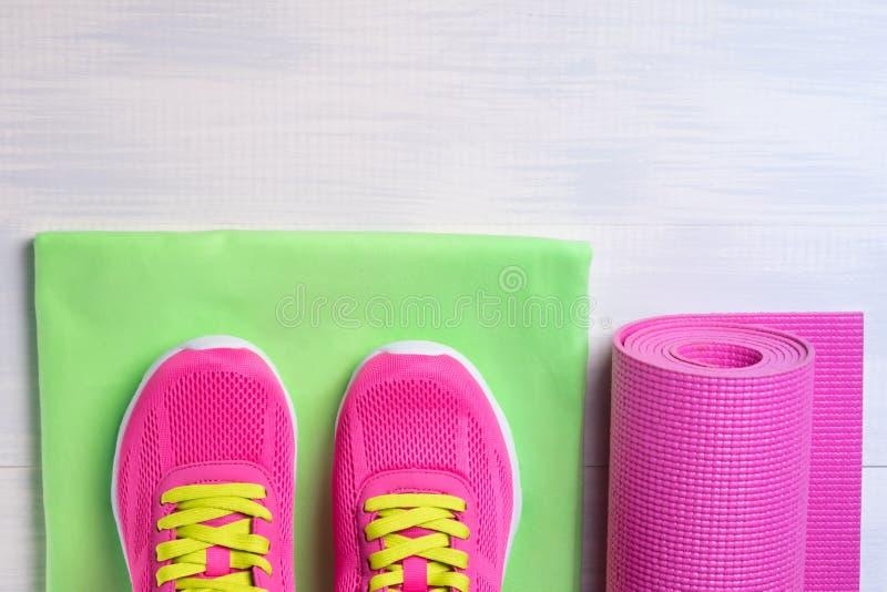 Πάνινα παπούτσια με μια κουβέρτα και πετσέτες για τον αθλητισμό στο ελαφρύ πάτωμα στοκ εικόνα