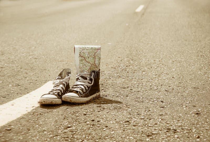Πάνινα παπούτσια στο δρόμο Δρόμος ταξίδι στοκ φωτογραφίες