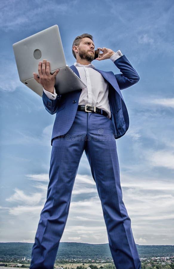 Πάντα στην αφή Ικανότητα επικοινωνίας Ο καλλωπισμένος επιχειρηματίας ατόμων καλά κρατά το lap-top ενώ μιλήστε το υπόβαθρο τηλεφων στοκ φωτογραφία με δικαίωμα ελεύθερης χρήσης